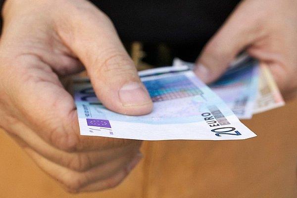 Roke, ki držijo oziroma izročajo evro bankovce.