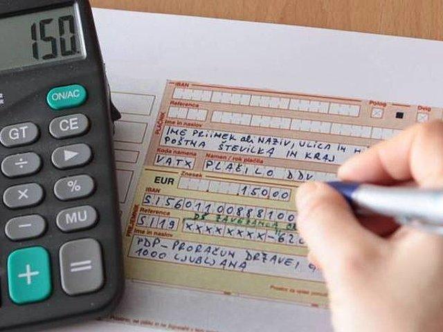 Ženska ročno izpolnjuje U P N nalog. Poleg je na mizi tudi kalkulator.