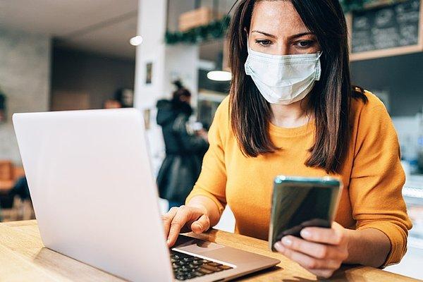 Ženska z zaščitno masko na obrazu sedi pri mizi in dela na prenosni računalnik. V eni roki drži mobilni telefon s katerega bere.
