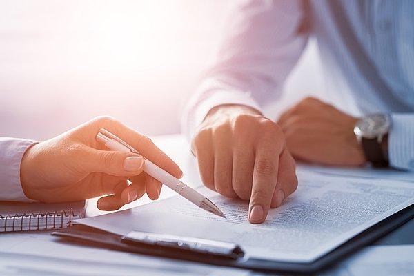 Poslovni ljudje. Človeške roke, ki delajo z dokumenti na mizi in podpisujejo pogodbo.