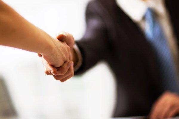 Poslovni ljudje se rokujejo, ko zaključujejo sestanek.