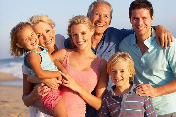 Portret družine treh generacij na počitnicah na plaži.